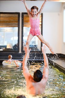 girl and dad playing in pool