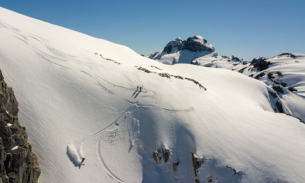 Group of skiers enjoy fresh powder from a heli-skiing adventure in Patagonia