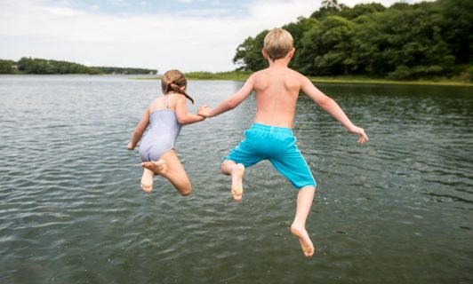 shelter beach kids jumping in water